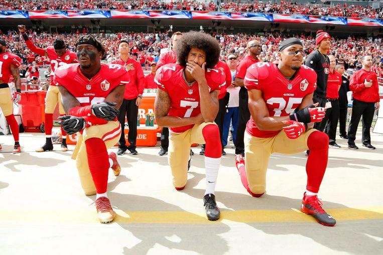Spelers van de San Francisco 49ers, met centraal quarterback en initiatiefnemer Colin Kaepernick, betuigen openlijk hun steun aan de Black Lives Matter-beweging door te knielen tijdens het volkslied, oktober 2016. Beeld EPA