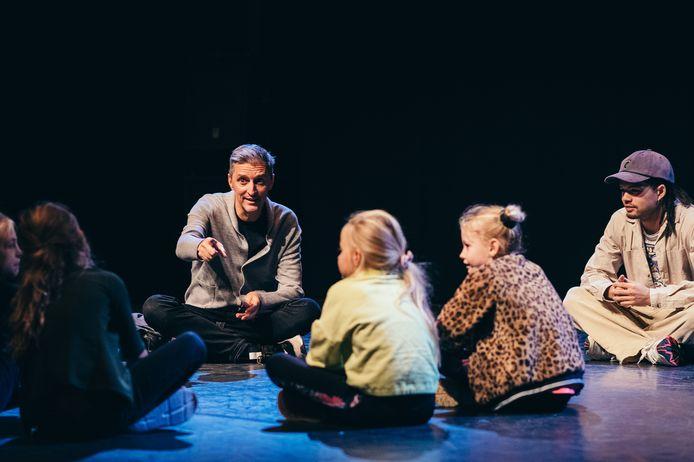 Adriaan Luteijn van Introdans (links) en choreograaf Ruben Chi (rechts) praten met kinderen na over de urban dancevoorstelling die Chi met de dansers van Introdans heeft gemaakt in het kader van de proeftuin jeugdtheater en -dans.