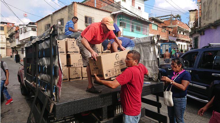 De annen laden bij gemeenschapshuis Casa Comunal 37 dozen met 360 eieren van de auto, de vrouwen regelen de distributie. Beeld Edwin Koopman