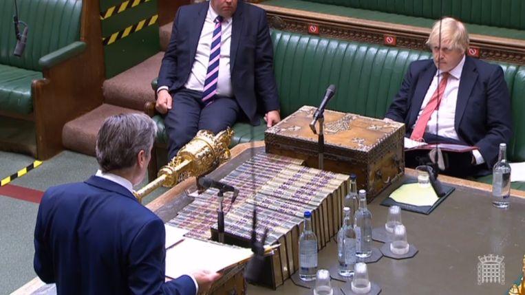 Labourleider Keir Starmer tijdens het wekelijkse vragenuurtje in het parlement, tegenover de onderuitgezakte premier Johnson.  Beeld EPA