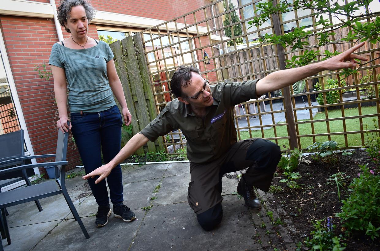 Boswachter Tim van den Broek legt buurvrouw Saskia van Dantzig , die een nieuw huis heeft gekocht, uit hoe ze de versteende tuin daar kan vergroenen.  Beeld Marcel van den Bergh