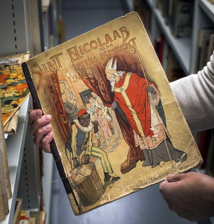 Een medewerker van de Openbare Bibliotheek Amsterdam (OBA) toont een boek met Sinterklaas en Zwarte Piet.