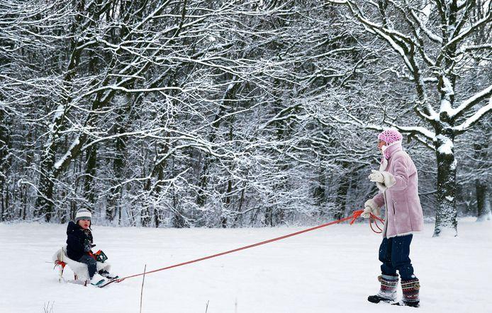 Een vrouw trekt een kind op een slee door de sneeuw. Foto ter illustratie.
