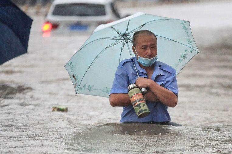 Een overstroomde straat in Zhengzhou. Beeld AFP