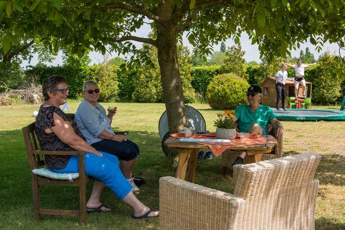 Petra Hoogland, Elodie Oppermans en Cees Hoogland onder de notenboom bij het huis van de Hooglands in Oostelbeers. Op de achtergrond spelen Elodies kleinkinderen.