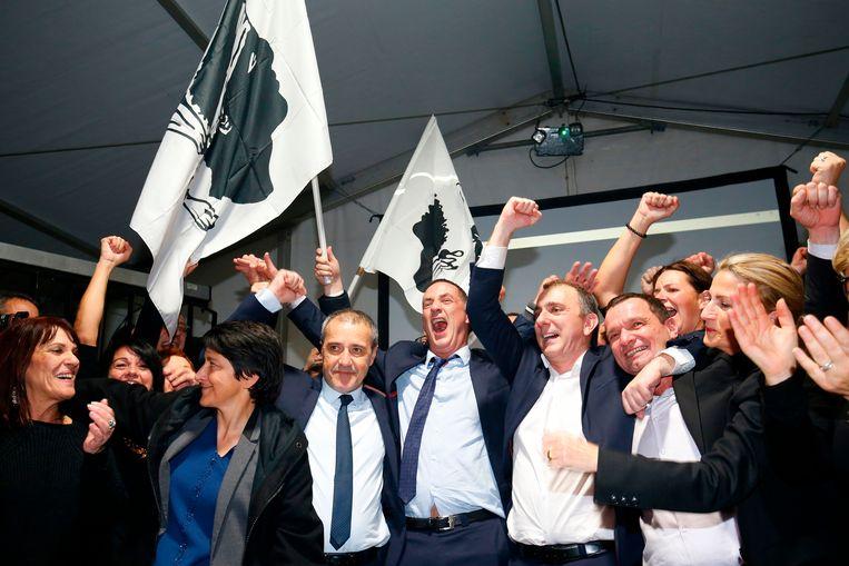 Vreugde bij de nationalisten Jean-Guy Talamoni (vierde van links) en Gilles Simeoni (vijfde rechts) op Corsica.  Beeld AFP
