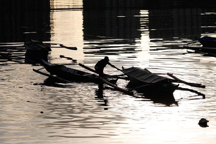 Een visser brengt zijn bootjes in veiligheid voor de naderende storm.
