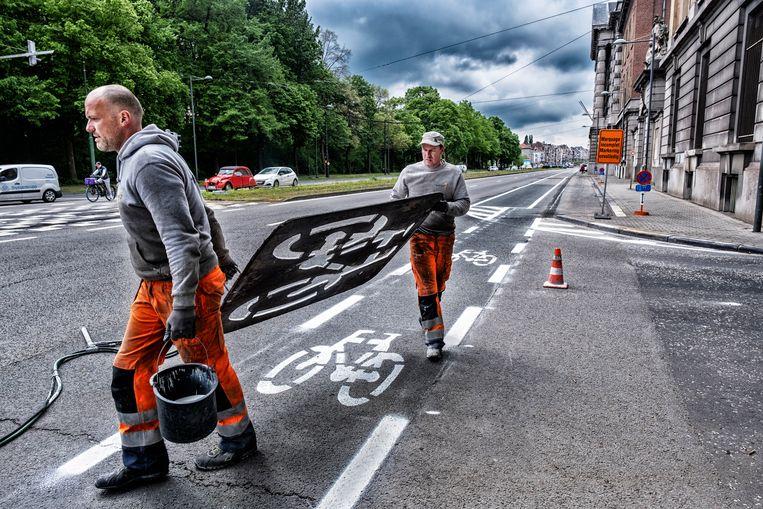 Een wegsignalisatieploeg markeert een nieuw fietspad in Brussel. Beeld Tim Dirven