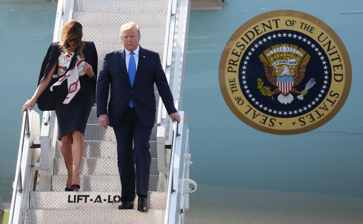 President Trump en zijn vrouw Melania dalen de vliegtuigtrap af na aankomst in Groot-Brittannië.