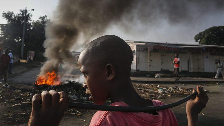 een jongen uit Burundi voor een brandende barricade tijdens een protestactie tegen president Pierre Nkurunziza. Beeld EPA