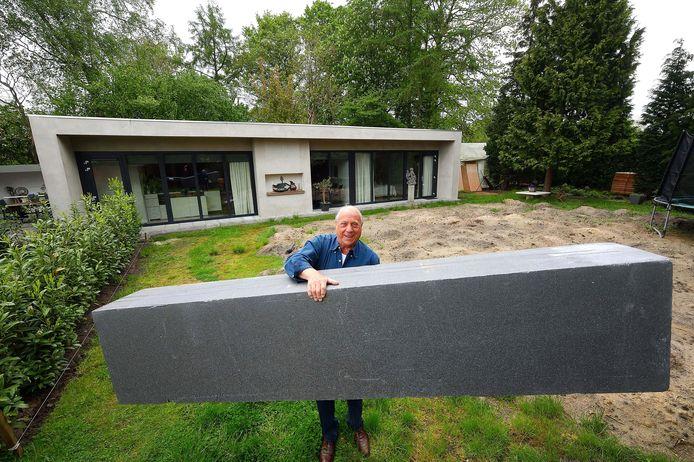 Piet van Heusen tilt moeiteloos de vederlichte Tempex-bouwblok, waarmee hij zijn huis op de achtergrond heeft gebouwd.