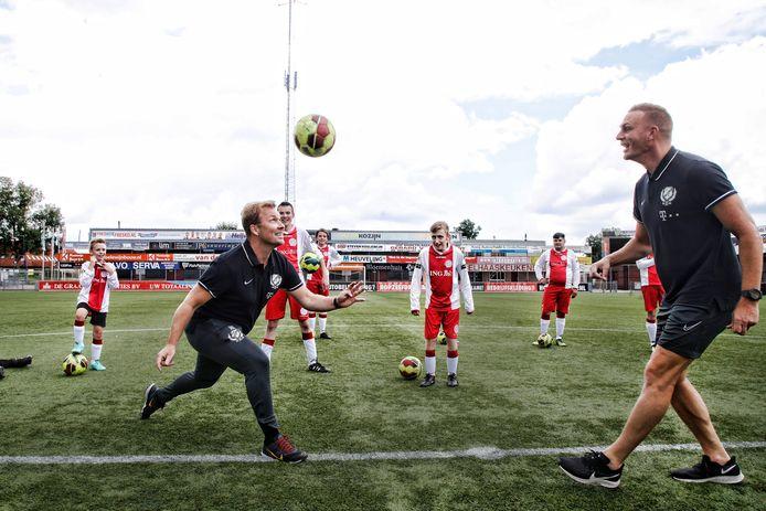 Rick Kruys (links) en Sander Keller, allebei assistent-trainer van FC Utrecht, doen een kopoefening voor op De Westmaat in Bunschoten-Spakenburg.