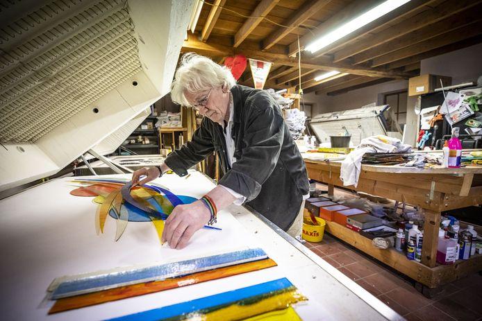 Frans Houben werkt in een van de grote ovens in zijn atelier aan een glaskunstwerk. Het is eindeloos passen, meten, schuiven, snijden. Daarna worden alle losse delen in de oven met elkaar versmolten.