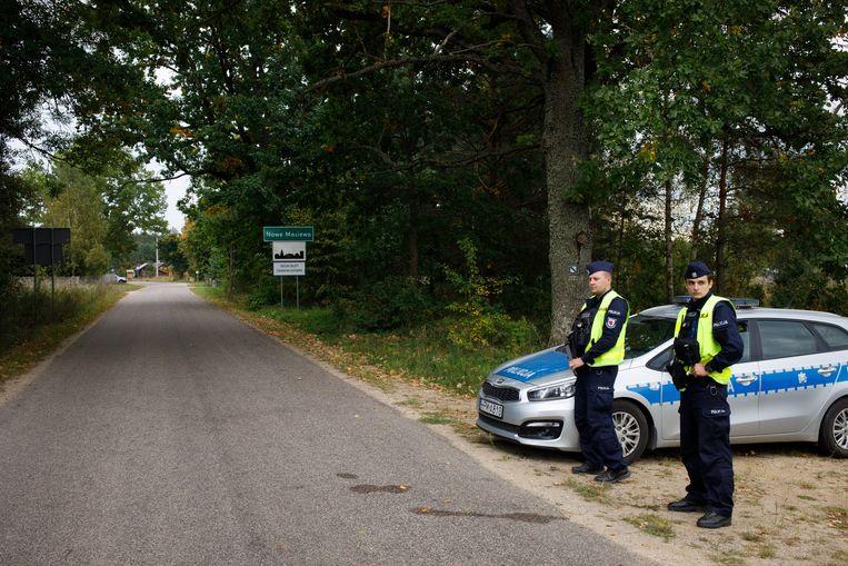 Agenten houden de toegangsweg naar Nowe Masiewo in de gaten, voor het gebied dat hier begint geldt de noodtoestand. Alleen inwoners worden doorgelaten. Beeld Piotr Malecki