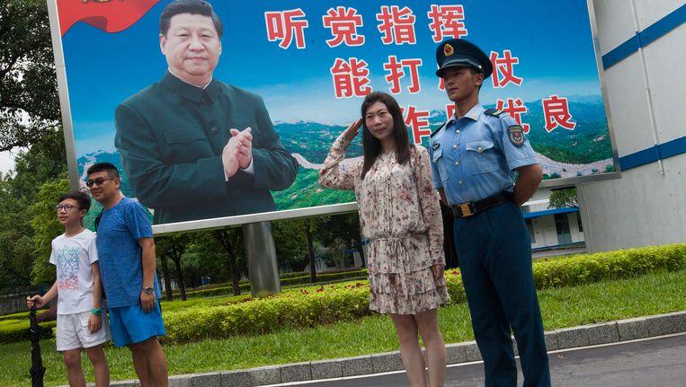 Een soldaat en enkele burgers poseren bij een afbeelding van president Xi Jinping in Hong Kong.