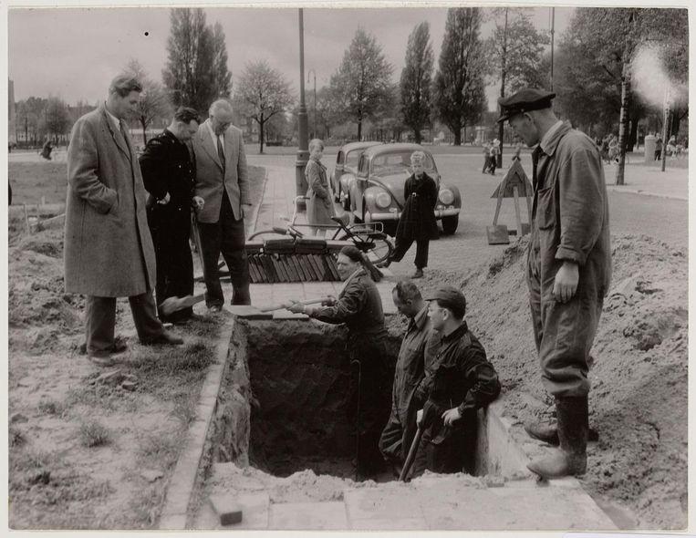 Mannen van de Mijnen Opruimingdienst en van de Bescherming Bevolking graven vlak na de oorlog in de Apollolaan een onontplofte bom uit. Beeld Gemeente Amsterdam