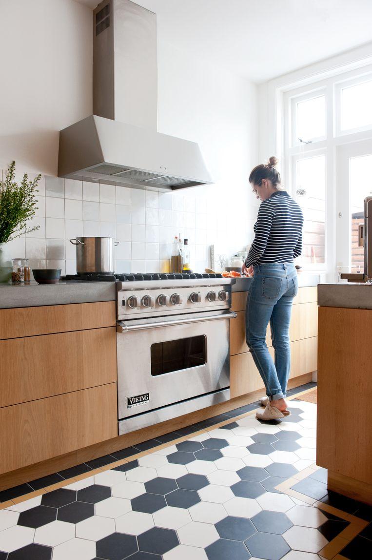 'Erik wilde graag een mannenkeuken, daarom hebben we een stoer zespitsgasfornuis. Hij heeft de inrichting van de keuken gedaan, ik mocht gelukkig de vloer kiezen. Het patroon vind ik erg mooi.' Beeld Anke Leunissen