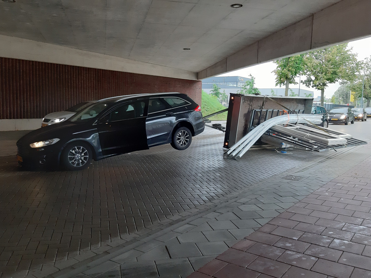 De auto met de omgevallen aanhanger.