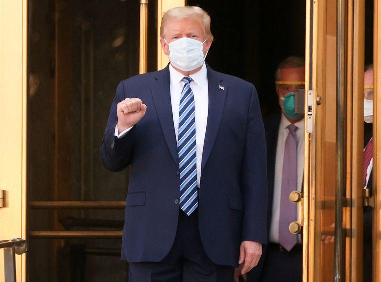 Met gebalde vuist en mondkapje op verlaat de Amerikaanse president Trump het Walter Reed National Military Medical Center. Beeld REUTERS