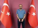 Een geboeide Selahaddin Gülen, neef van de islamitische geestelijke Fethullah Gülen, poserend tussen Turkse vlaggen op een foto verspreid door de Turkse inlichtingendienst.