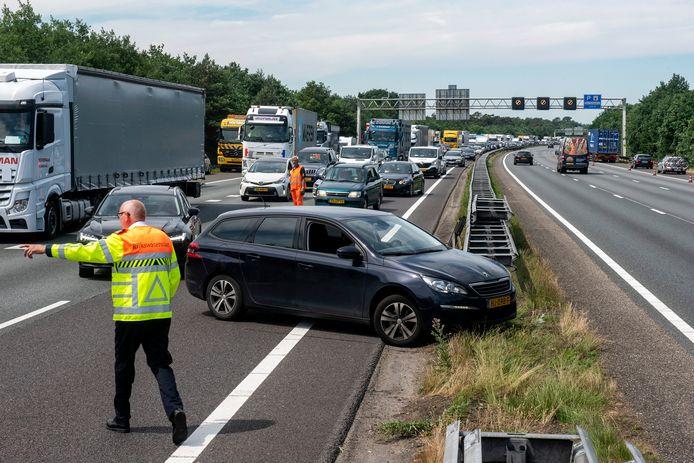 Achter het ongeluk op de A12 gestrande automobilisten worden weggeleid via de andere rijbaan.