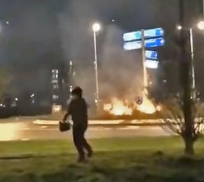 De jongere komt teruggelopen met een jerrycan in zijn hand, nadat hij even daarvoor de bosjes op een rotonde in Leerdam in brand stak.