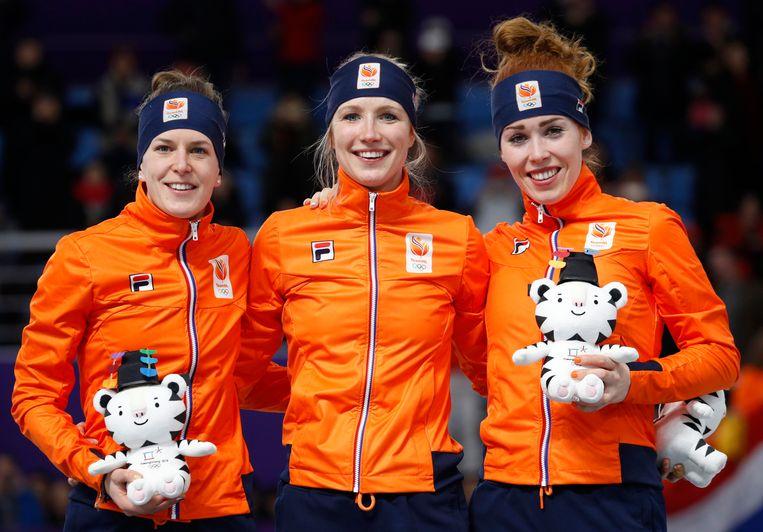 Ireen Wust, Carlijn Achtereekte en Antoinette de Jong op het Oranje-getinte podium van de olympische 3 kilometer. Beeld AP