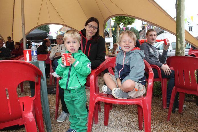 Enkele kinderen genieten beschut van de regen van een drankje.