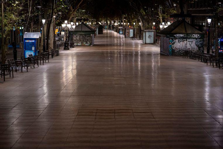 De Ramblas, gewoonlijk gevuld met terrasjes, kraampjes en mensen, zijn leeg. Beeld AP