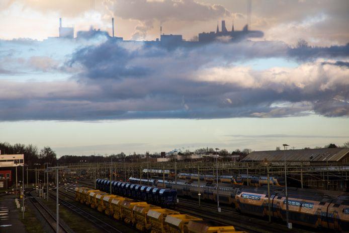 Het Roosendaalse treinstation met in de wolken het stadssilhouet met onder meer de schoorsteen van Philips en de torens van de Paterskerk.