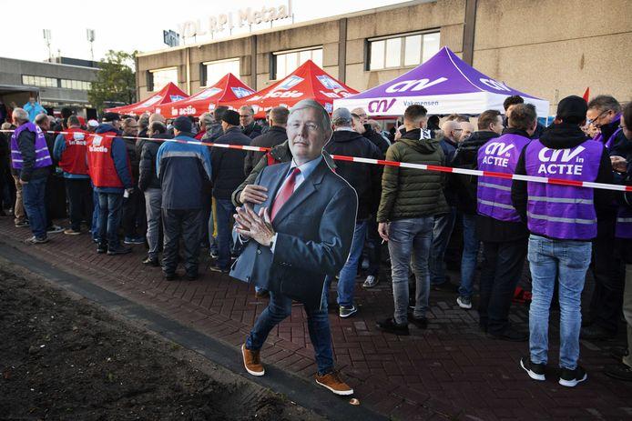 Werknemers schrijven zich in als staker bij de poorten van VDL. Iemand draagt een bord van werkgeversvoorman Ab van der Touw.