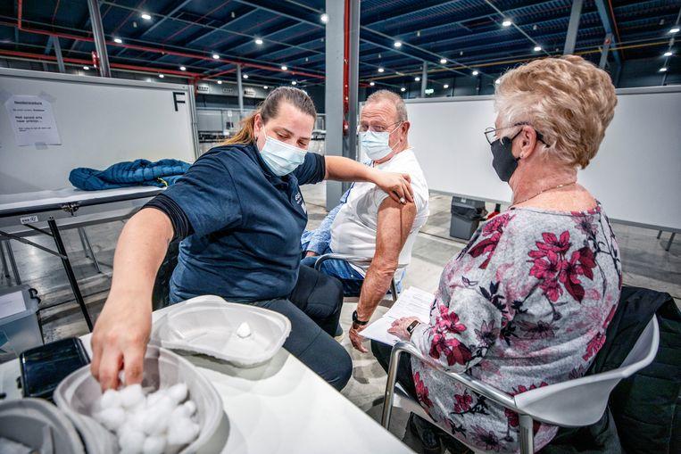 Henk en Tini de Groot uit Nieuwegein worden gevaccineerd op de priklokatie van de GGD in de Utrechtse Jaarbeurs. Beeld Raymond Rutting / de Volkskrant