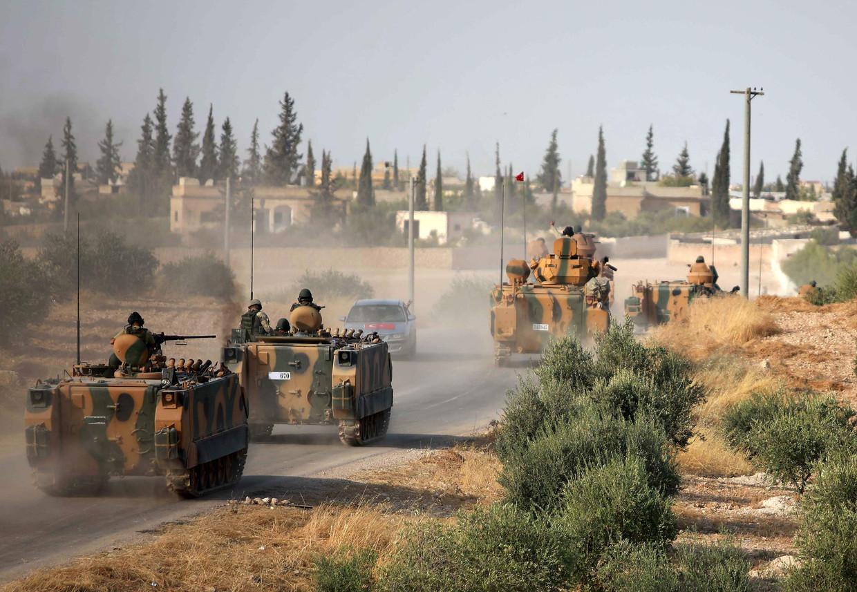 Turkse troepen rijden Qiratan, nabij de stad Manbij, binnen.  Beeld AFP