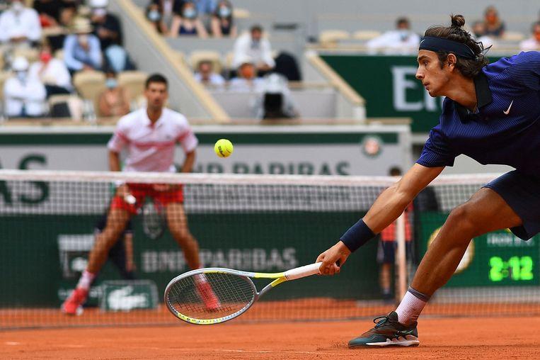 Lorenzo Musetti retourneert de bal in zijn partij tegen Novak Djokovic. Het Italiaanse talent zou een 2-0-voorsprong verspelen. Beeld AFP