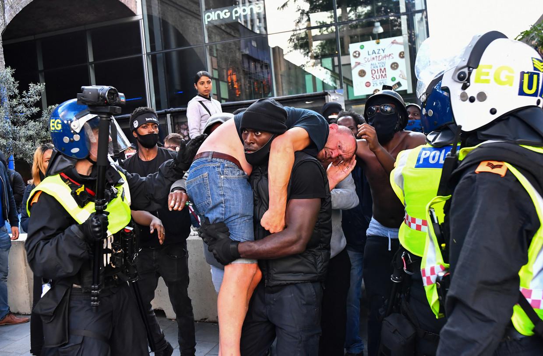 De iconische foto. Patrick Hutchinson draagt de onwel geworden tegendemonstrant weg om hem in veiligheid te brengen. Beeld REUTERS