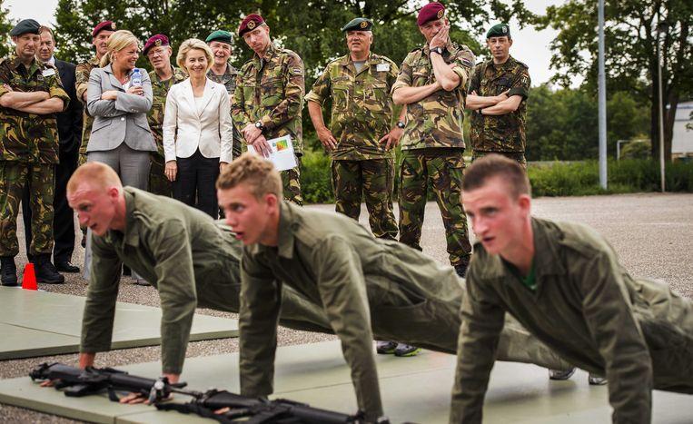 Ministers van Defensie Jeanine Hennis-Plasschaert (L) en Ursula von der Leyen bekijken een static show tijdens de integratie van de Luchtmobiele Brigade met de Duitse Division Schnelle Krafte in Schaarsbergen. Beeld ANP