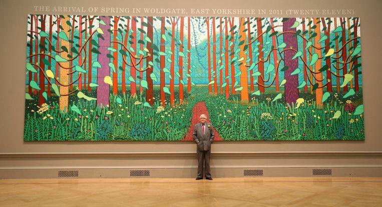 David Hockney in 2012 bij zijn schilderij 'The Arrival of Spring in Woldgate, East Yorkshire in 2011 (twenty-eleven). Beeld Getty Images