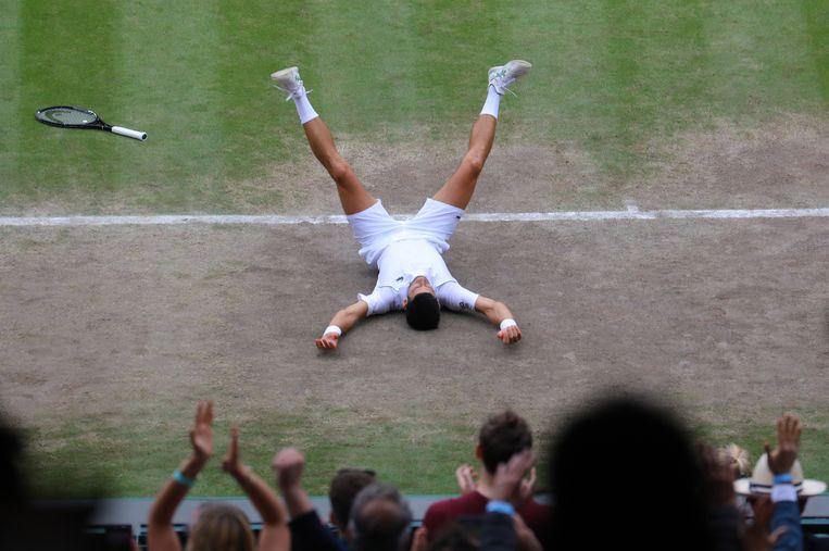 Novak Djokovic laat zich na het winnende punt vallen op het gras van Wimbledon. Beeld EPA