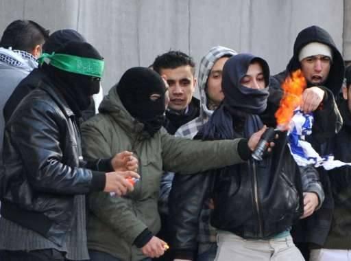 Gemaskerde demonstranten steken de Israëlische vlag in brand.