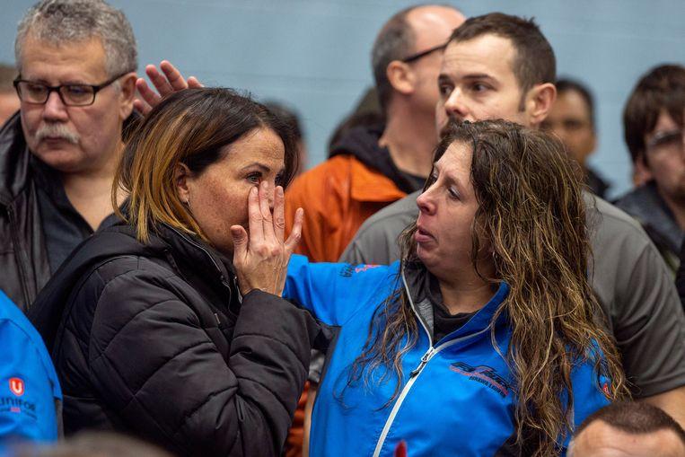 Medewerkers van General Motors in Canada zoeken troost bij elkaar nadat ze hebben gehoord dat sluiting dreigt voor hun fabriek.  Beeld Reuters
