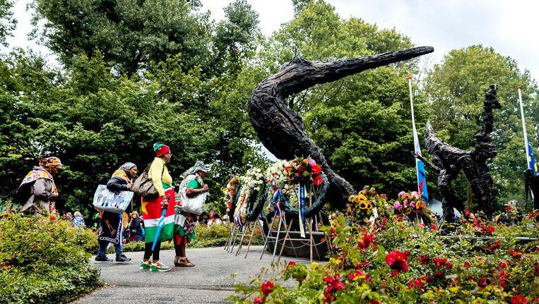 Bezoekers bij het Nationaal Monument Slavernijverleden tijdens de nationale herdenking van de afschaffing van de slavernij in het Oosterpark. Beeld anp