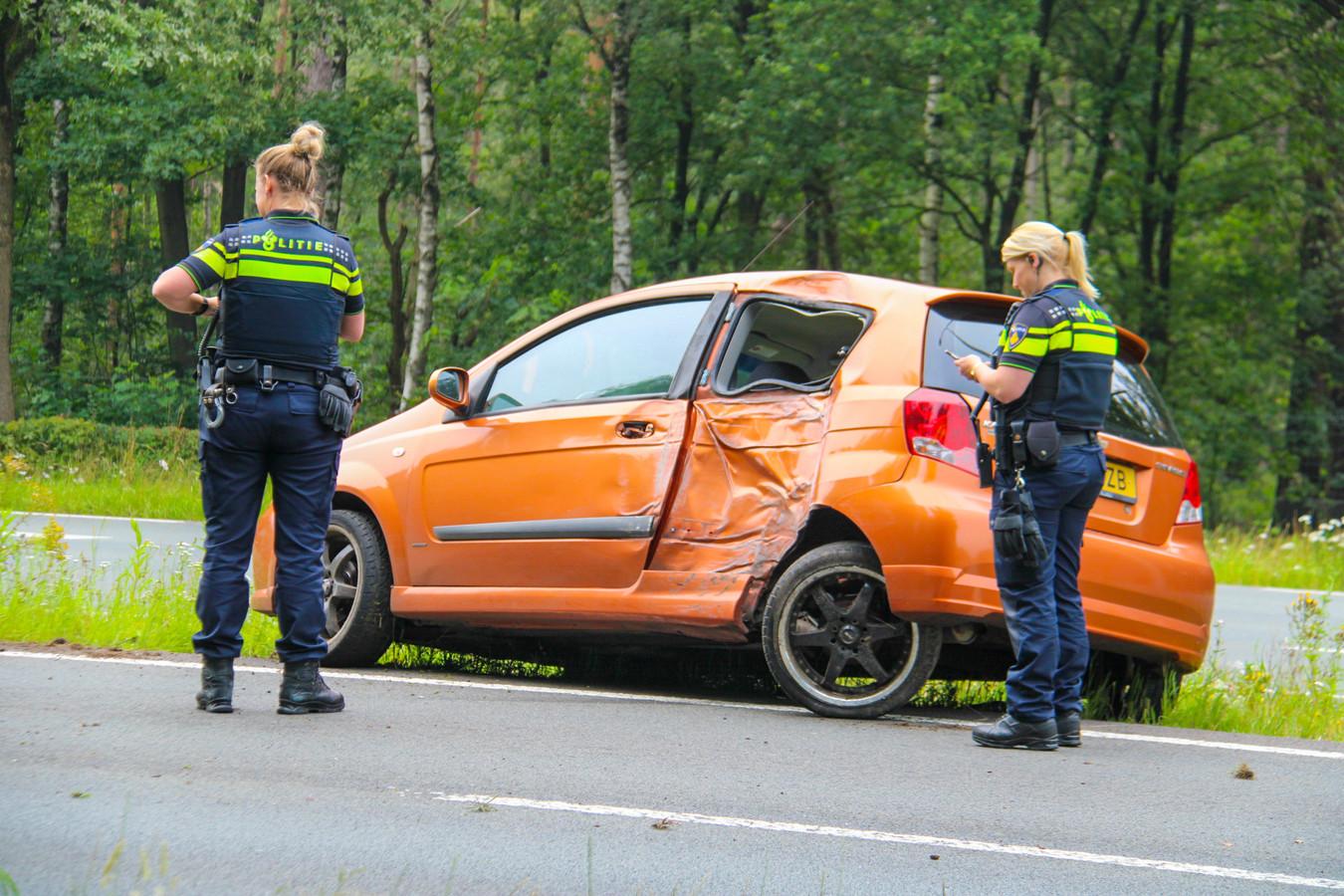 Politieagenten noteren de schade aan weg en omgeving met op de achtergrond de zwaarbeschadigde auto.