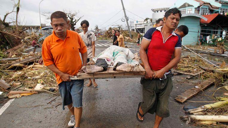 Overlevenden dragen een slachtoffer van de tyfoon door de puin in Tacloban Beeld REUTERS