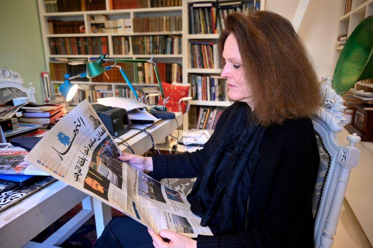 Monika Borgmann, de weduwe van Lokman Slim, leest een artikel in een Libanese krant over de moord op haar man.   Beeld Wael Hamzeh / EPA