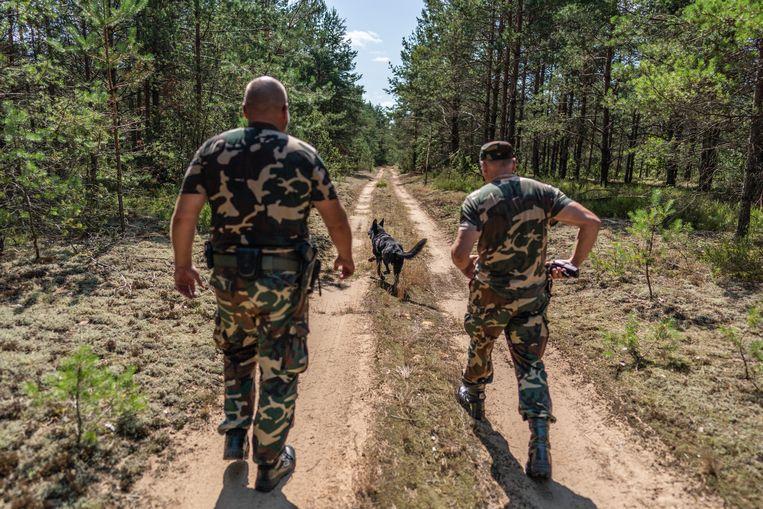Bewapende leden van de Litouwse grensbewaking controleren de grens met Belarus. Beeld Joris van Gennip