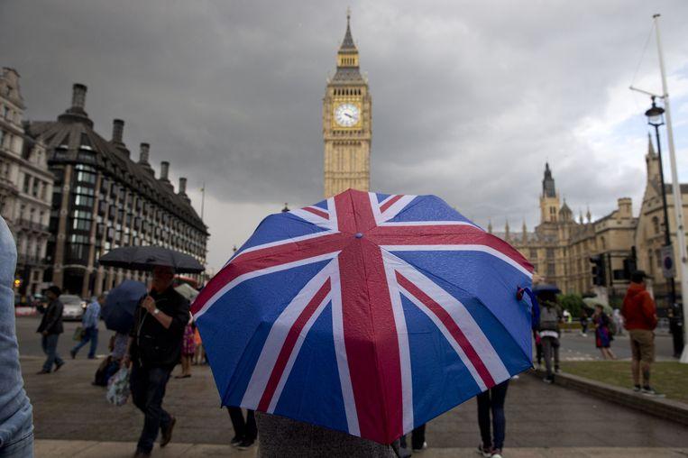 Een voetganger schuilt voor de Londense regen onder een paraplu met de Britse vlag voor de Big Ben, de klokketoren die momenteel wordt gerenoveerd. Beeld AFP