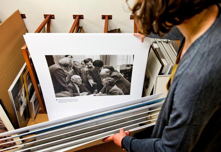 Beheerder van het kunstdepot van de Tweede Kamer Hasna Bajraktarevic bekijkt een werk van fotograaf Dolf Toussaint. Beeld Guus Schoonewille