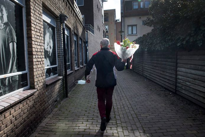 Wat een blij loopje: In een steeg in Tiel zag de fotograaf deze man met een boeket, en een mondkapje in zijn linkerhand. 'Wat me trof? Het blije loopje, en het zonlicht dat de bloemen streelt.'