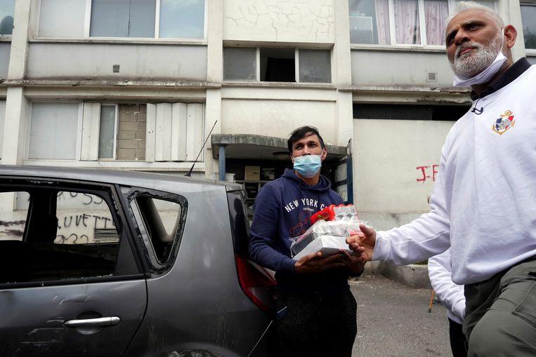 Kapitein Nourouddine Abdoulhoussen deelt maaltijden uit aan armen en daklozen in Pierrefitte-sur-Seine, net buiten Parijs.   Beeld Thibault Camus / AP