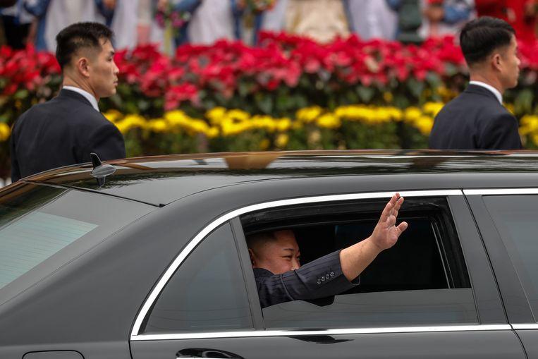 Kim zwaait vanuit zijn gepantserde limousine waarmee hij doorreist naar Hanoi. Beeld EPA